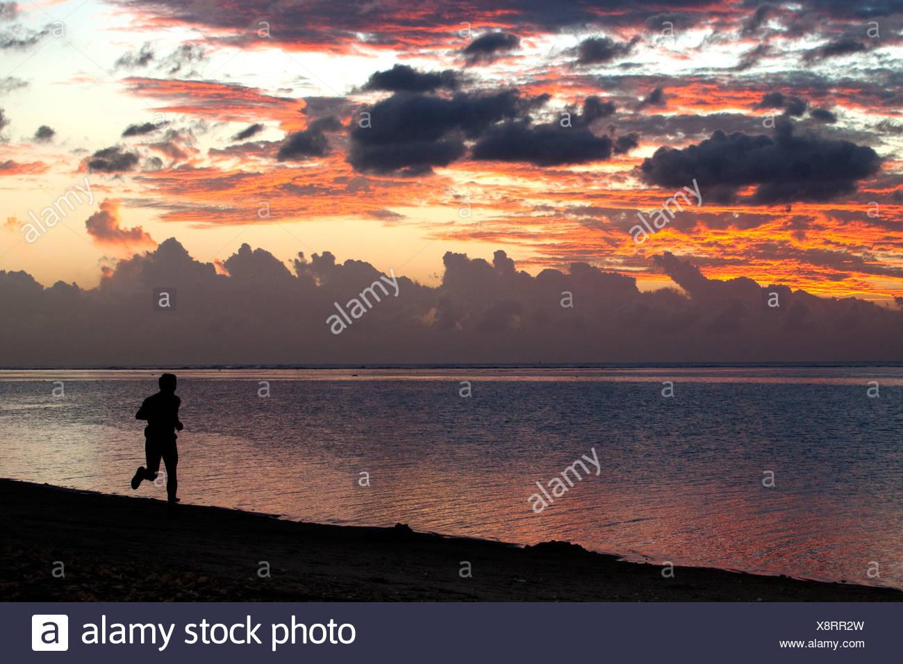 Man jogging at sunset on the beach of Saline-les-Bains, La Reunion island, Indian Ocean - Stock Image