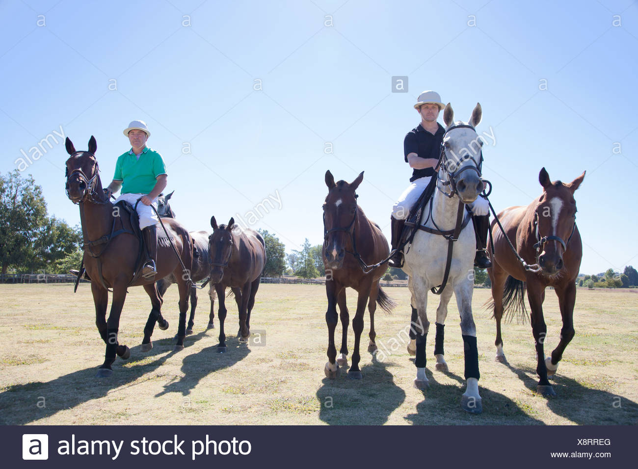 Polo players, leading horses in from field - Stock Image
