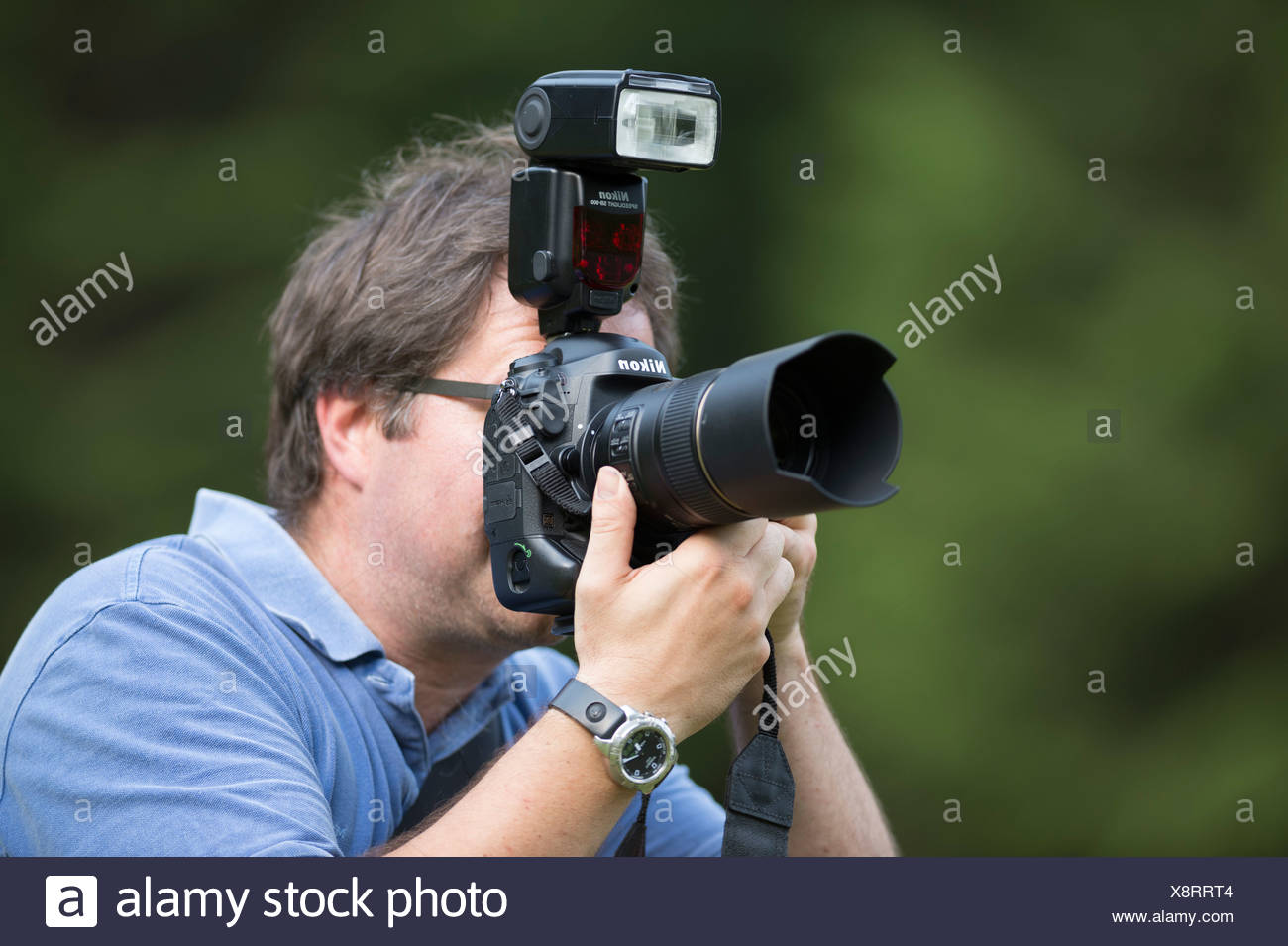Photographer, mid 40's, taking pictures, looking through the viewfinder of a Nikon D4 digital SLR camera with a shoe-mounted - Stock Image