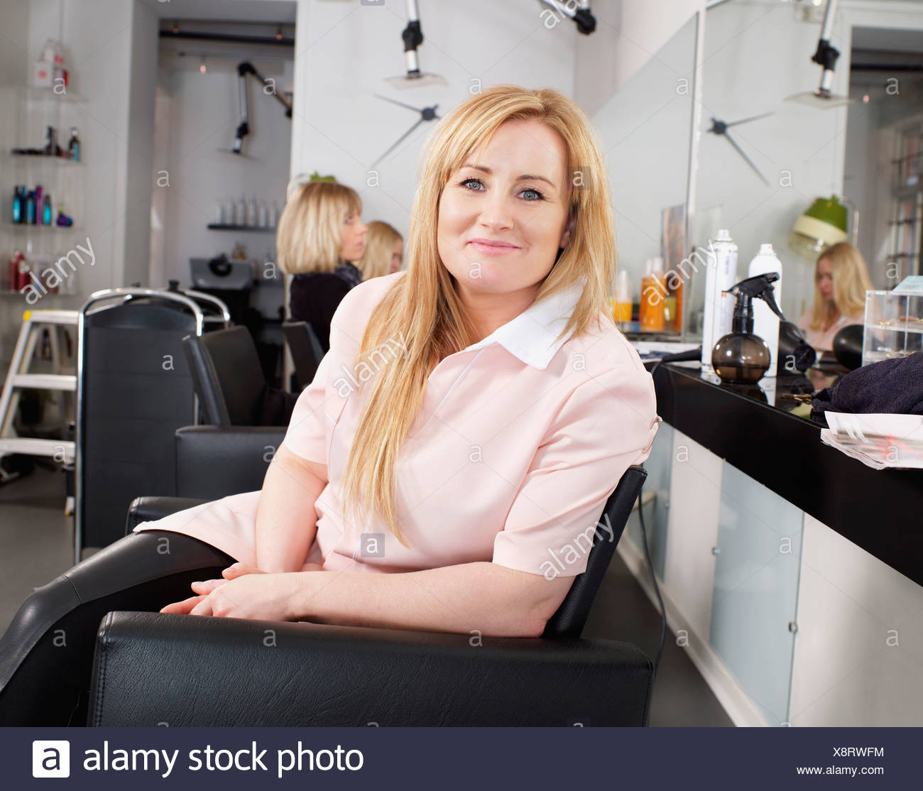 Hairdresser sitting in salon chair - Stock Image