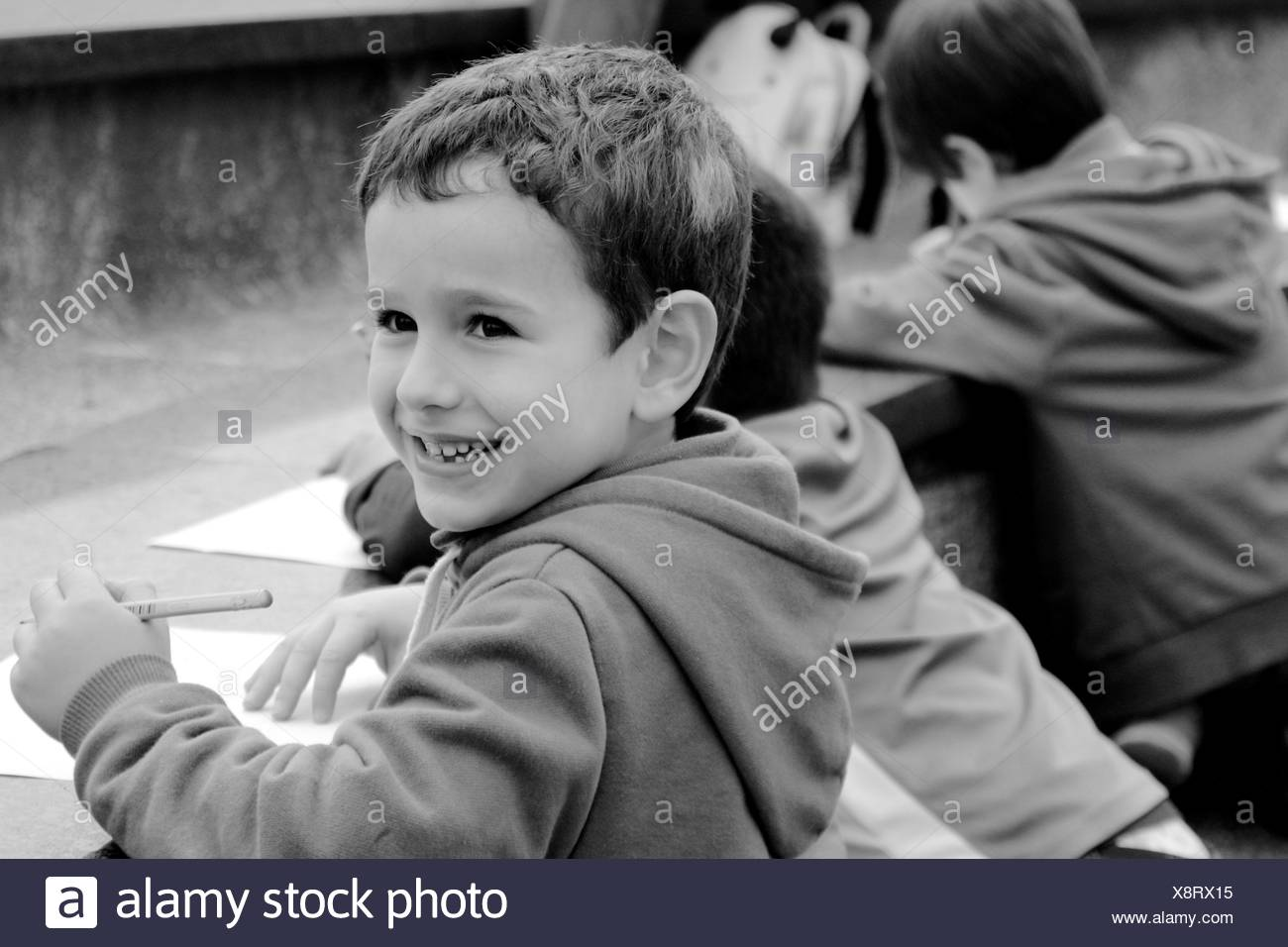 China, Hong Kong Island, Hong Kong, Boy (4-5) smiling while drawing, people in background - Stock Image