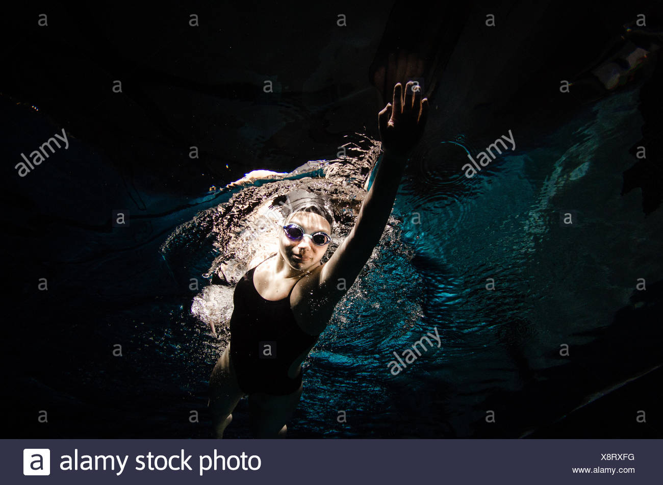 A young woman in a black bathing suit, black swim cap and goggles swims freestyle. - Stock Image