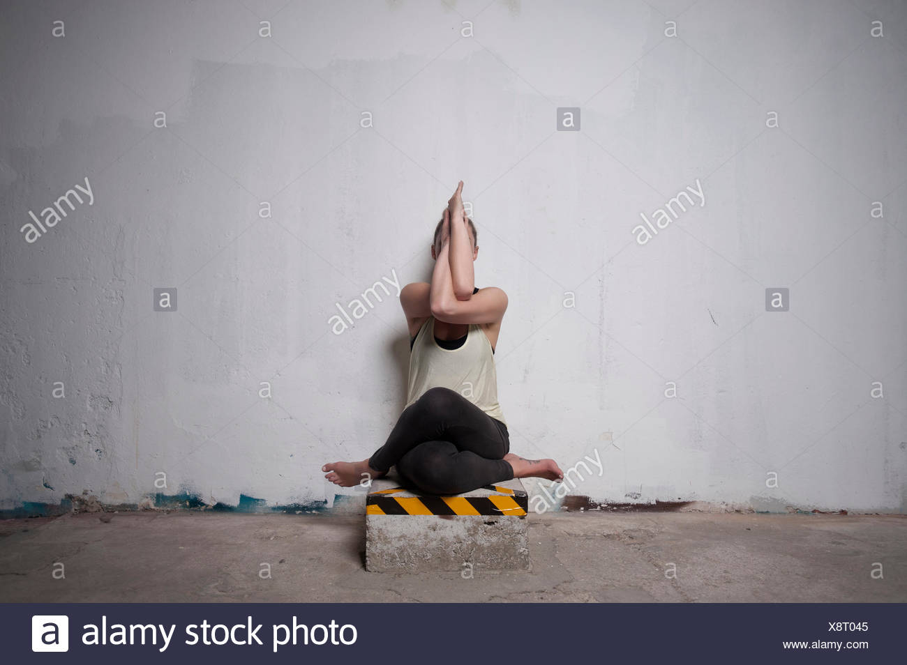 Mid adult woman practicing cow face pose in yoga studio, Munich, Bavaria, Germany - Stock Image
