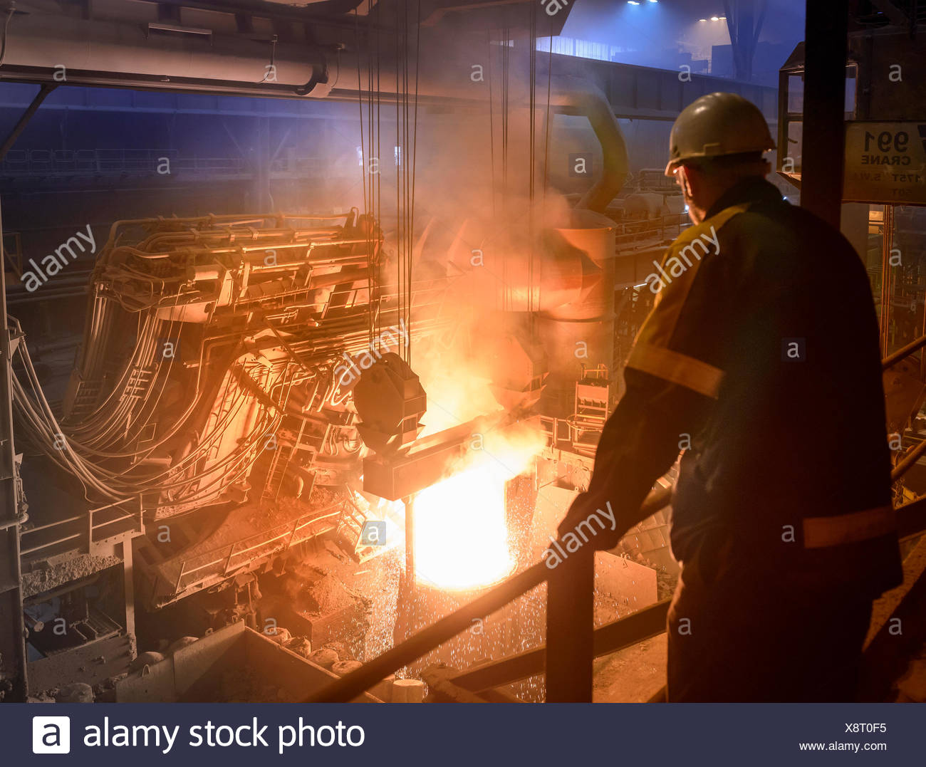 Steel worker inspecting pouring molten steel - Stock Image