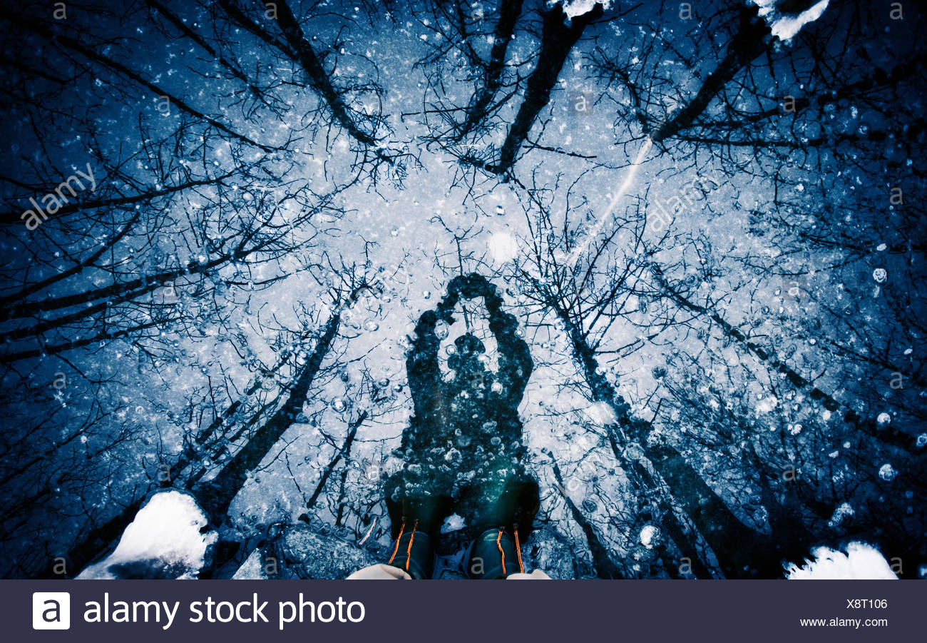 A man holding an object above his head, a shadow on the surface of ice. - Stock Image