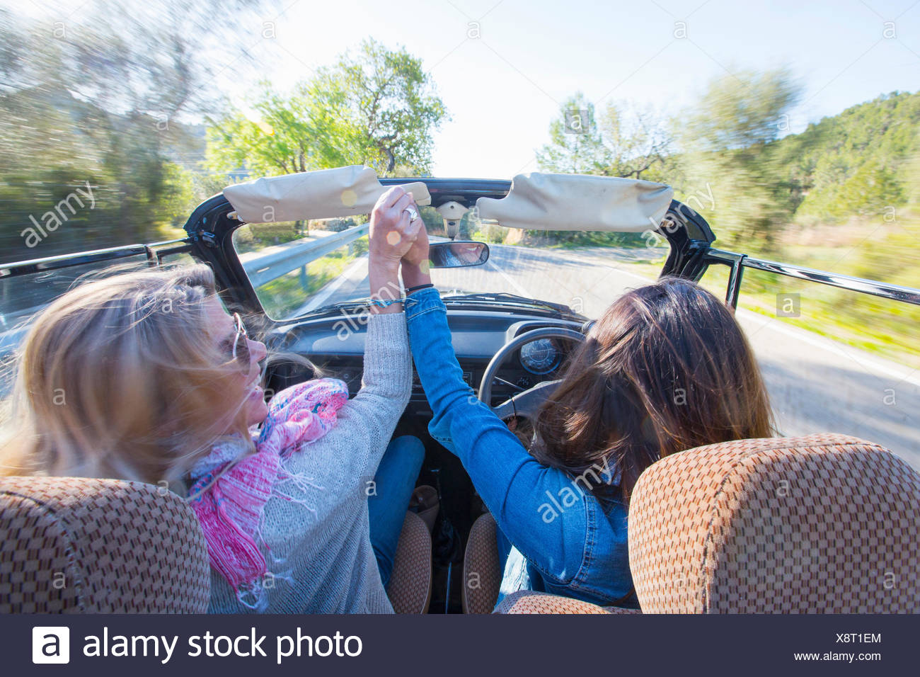 Two mature women, holding hands, in convertible car, rear view - Stock Image