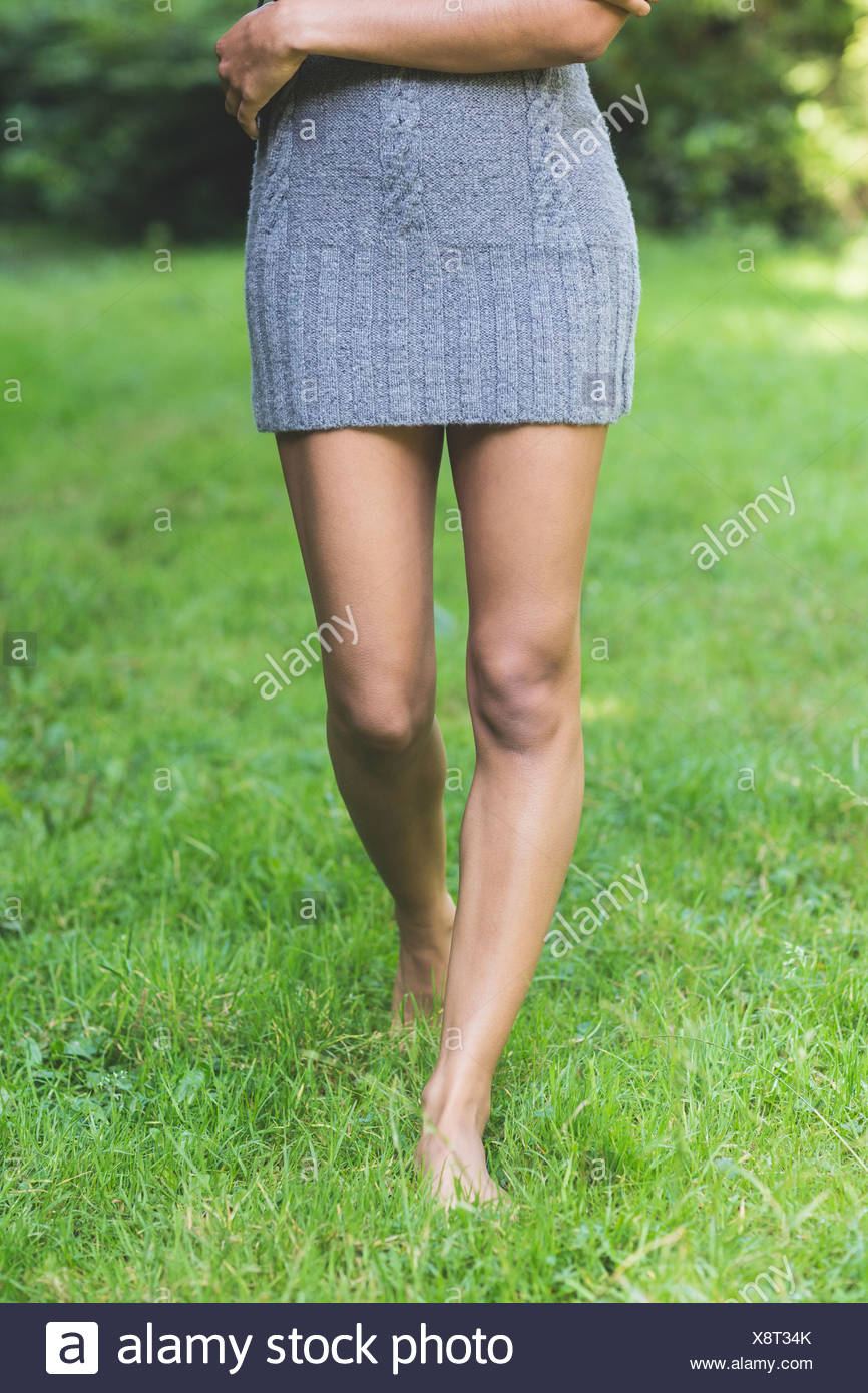 Lower body of attractive model walking on grass - Stock Image