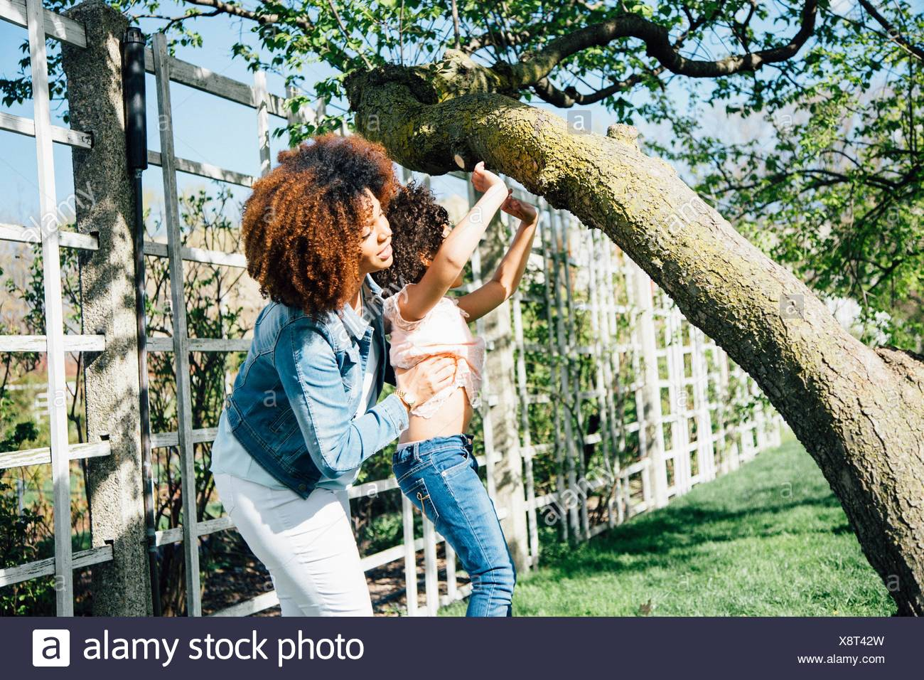 Side view of mother helping daughter to climb tree - Stock Image