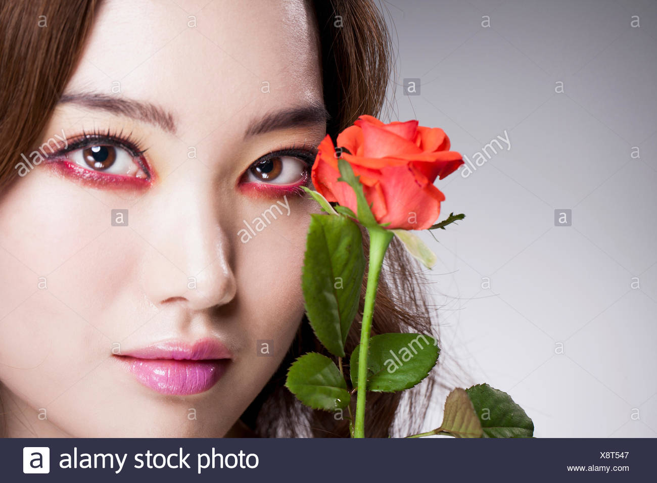 Portrait of young Korean woman in rwd eye liner posing with a red rose - Stock Image