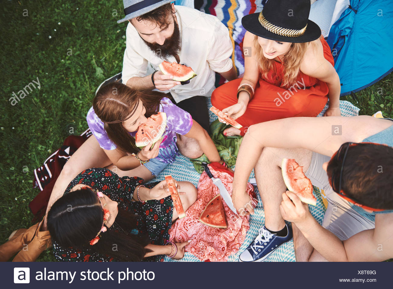 Overhead view of young boho adult friends eating melon slices at festival - Stock Image