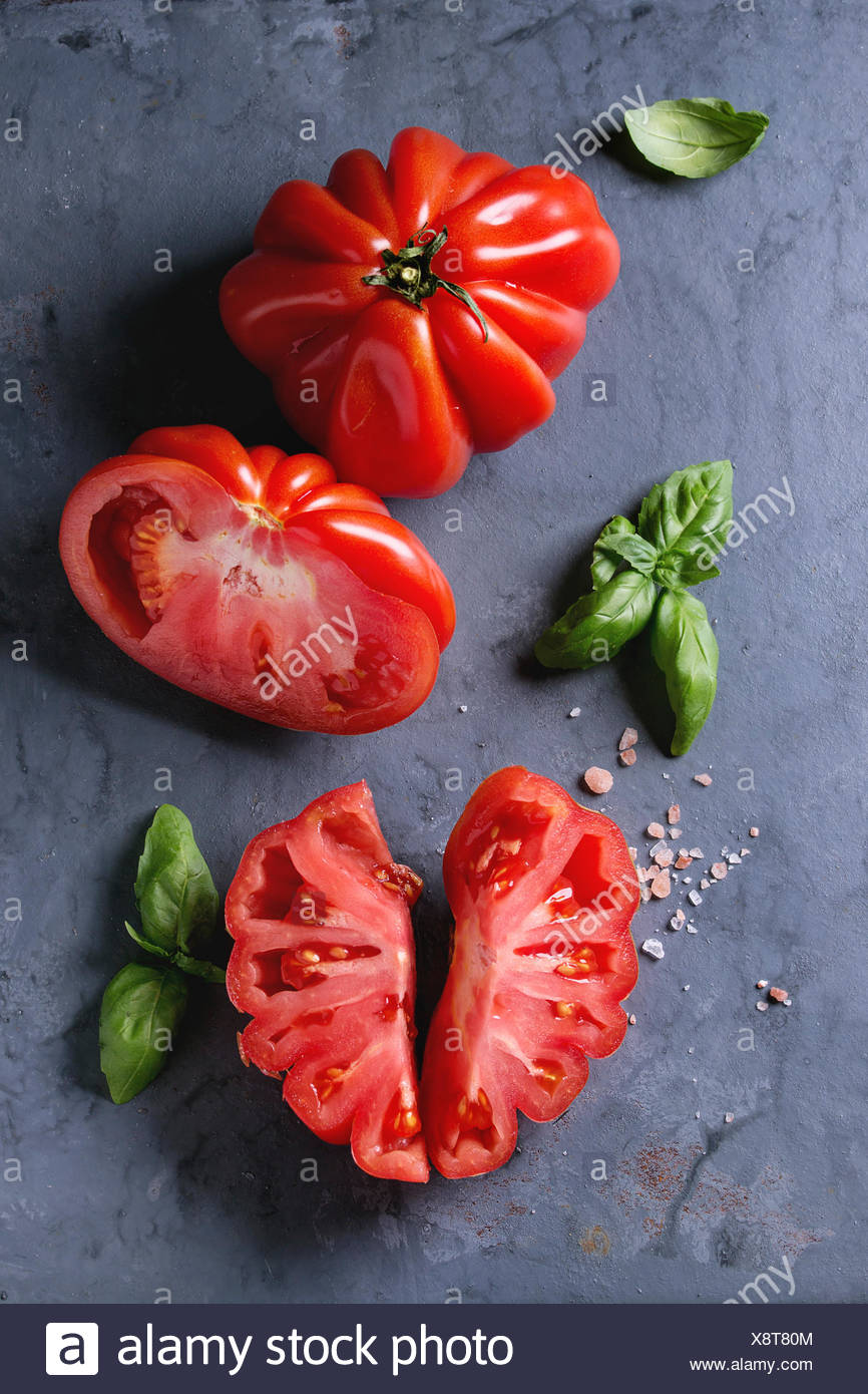 Whole and sliced organic tomatoes Coeur De Boeuf. Beefsteak tomato with pink salt and basil on blue gray metal texture background. Top view with space Stock Photo