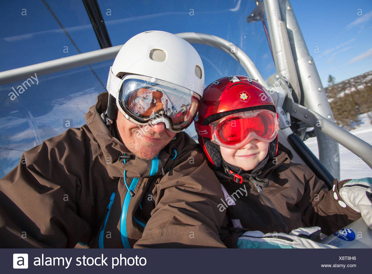Norway, Osterdalen, Trysil, Portrait of girl (4-5) and her father taking ski lift - Stock Image
