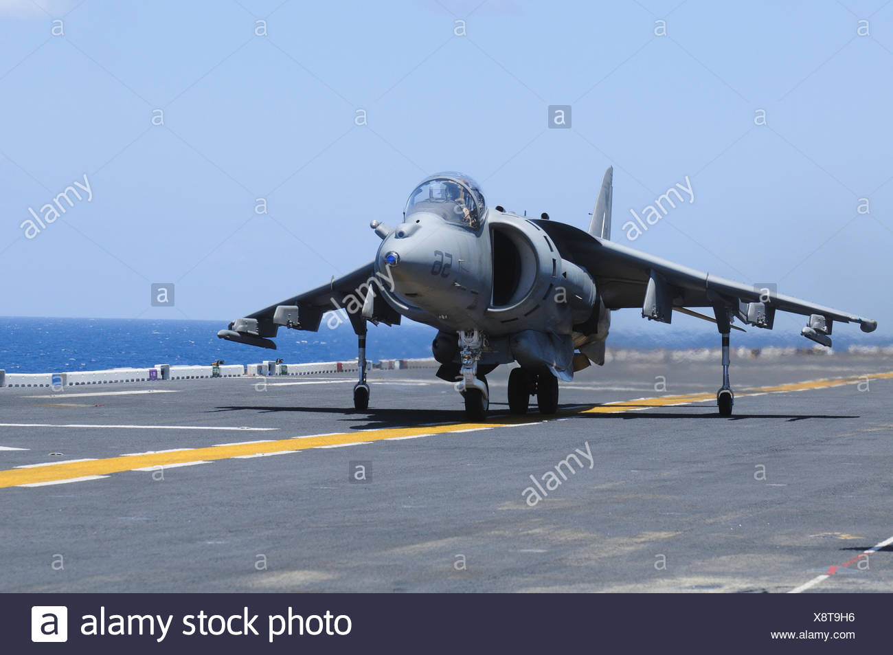 An AV-8B Marine Harrier II lands on the flight deck of the USS Peleliu (LHA-5) during flight operations in the Pacific Ocean Stock Photo