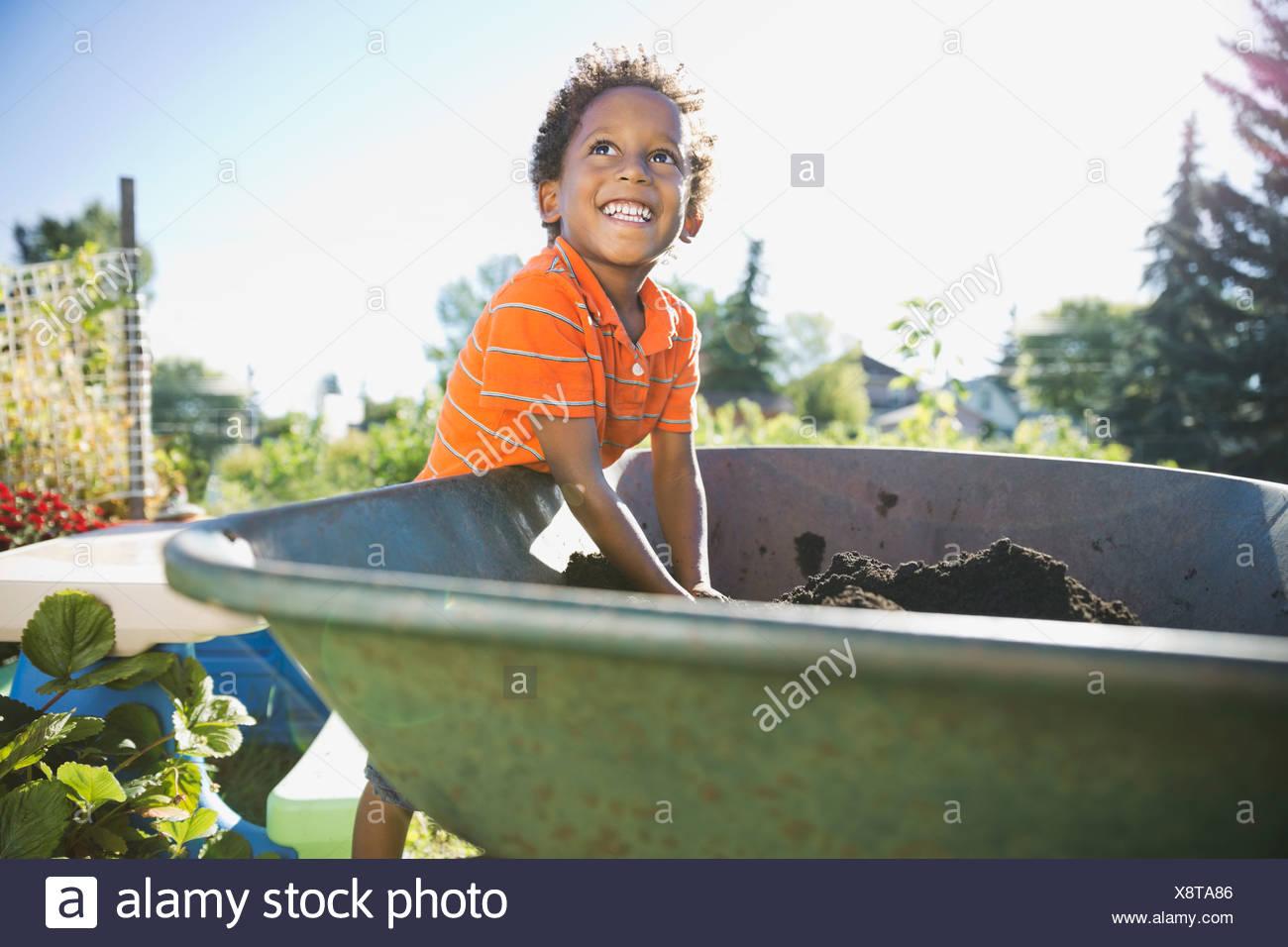 Boy picking up garden dirt in wheelbarrow - Stock Image
