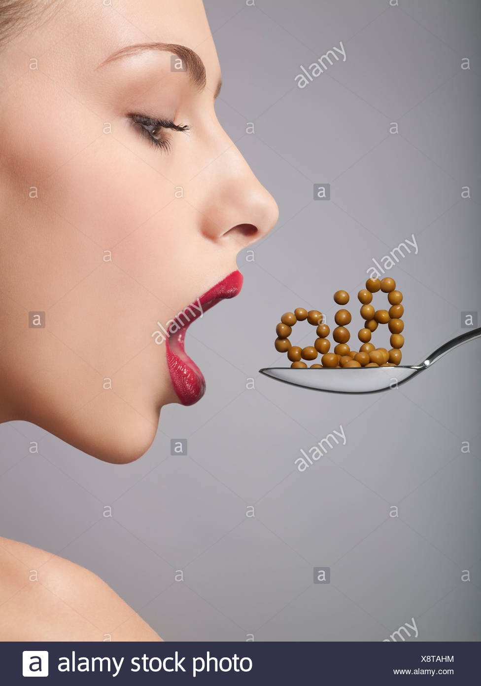 A woman eating bio cereal from a spoon, side view - Stock Image