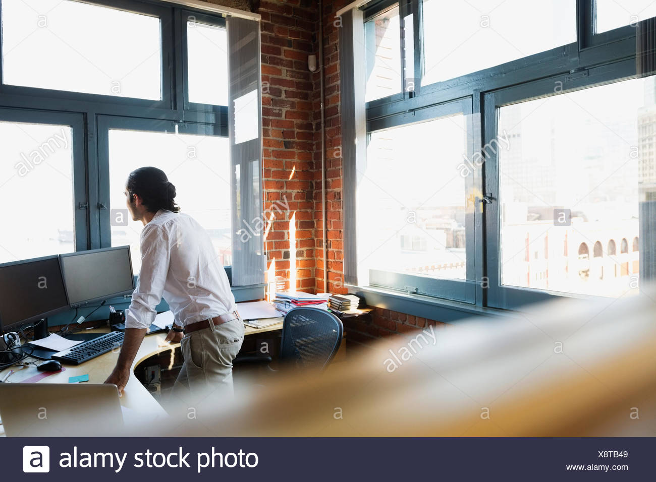 Pensive Businessman Looking Out Office Window   Stock Image