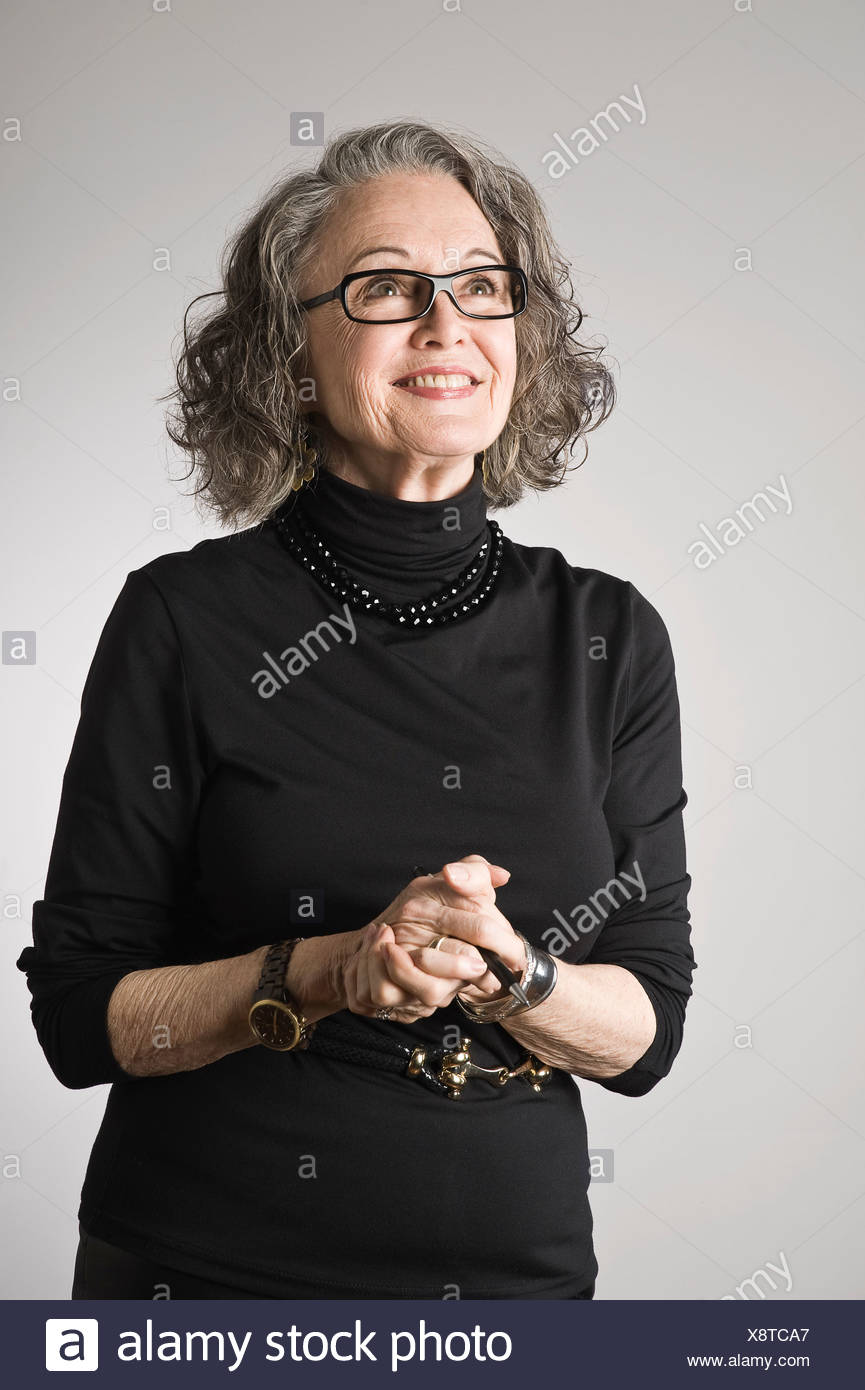 Portrait of senior woman, looking up - Stock Image