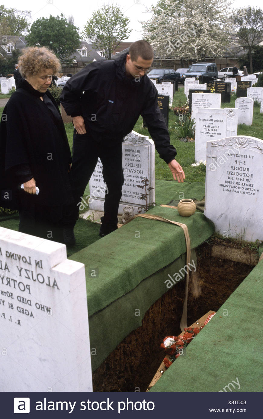 Burial scene in church cemetery where moarners drop soil on the coffin - Stock Image