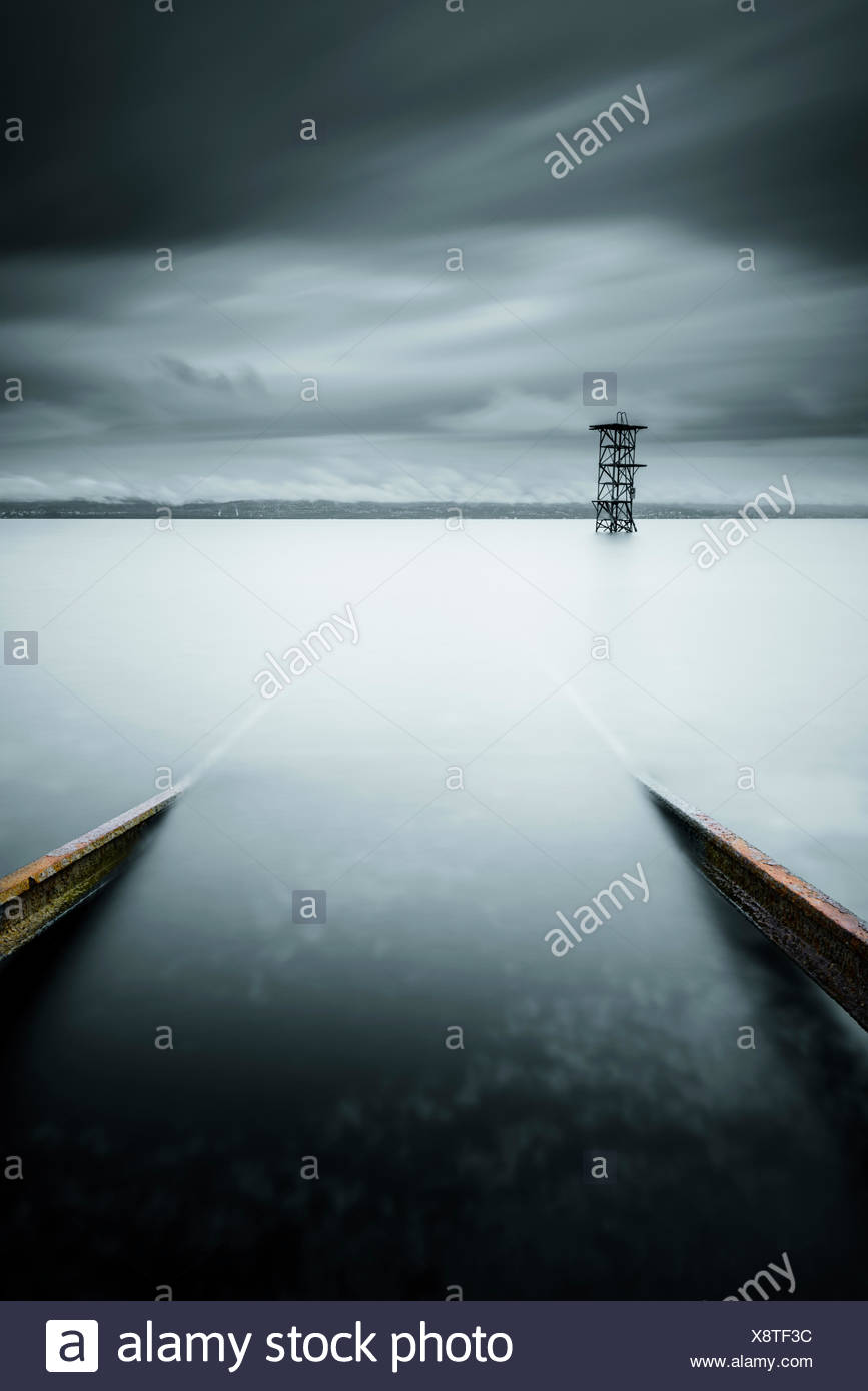 Switzerland, Vaud, Saint-Prex, Lake Leman, Slipway in still lake with storm clouds - Stock Image