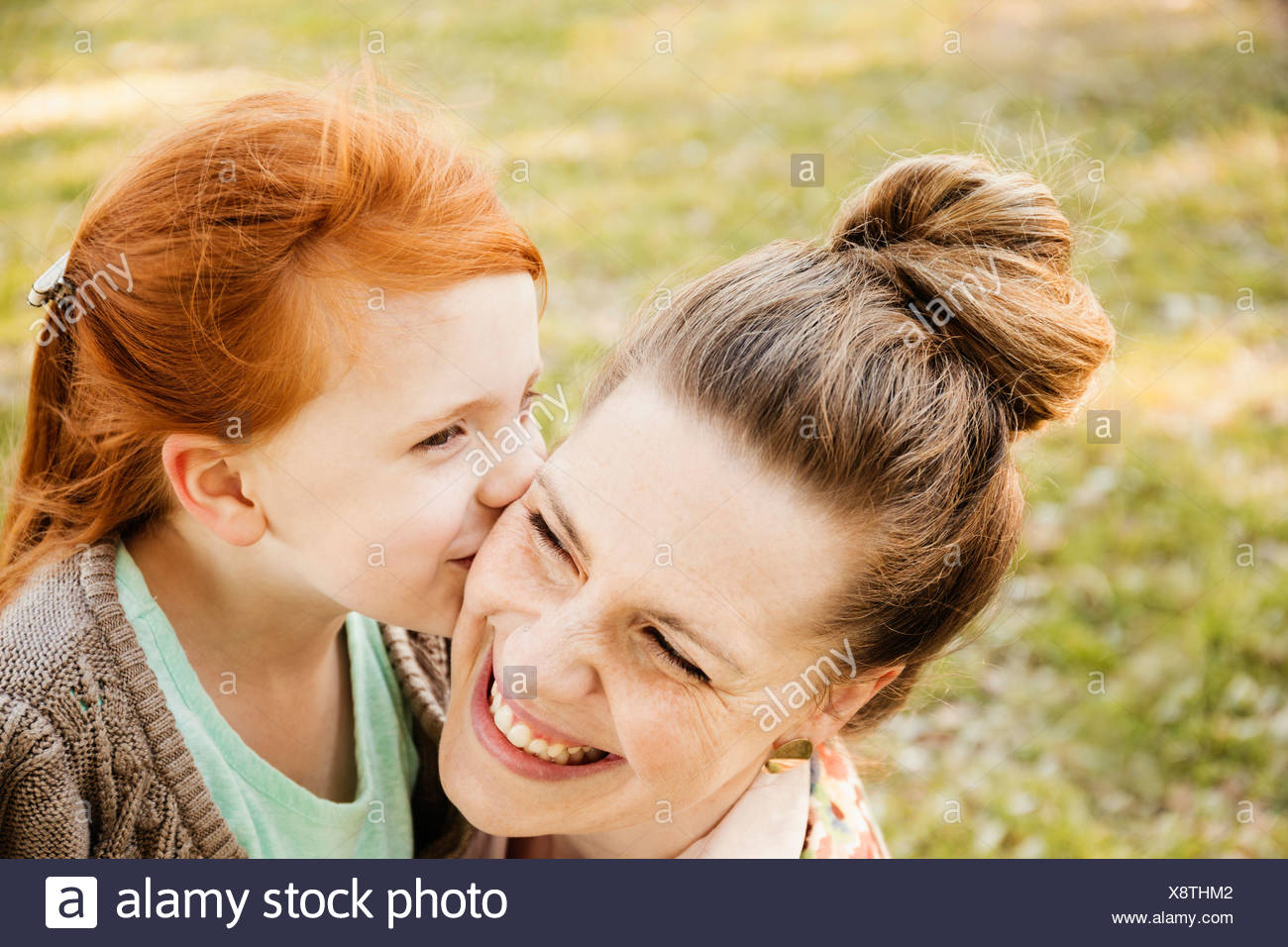 Portrait of smiling mid adult mother and daughter in park - Stock Image