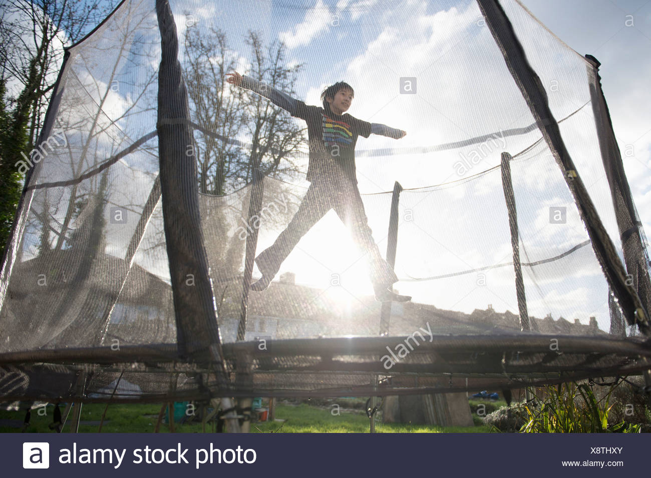 Boy jumping on outdoor trampoline - Stock Image