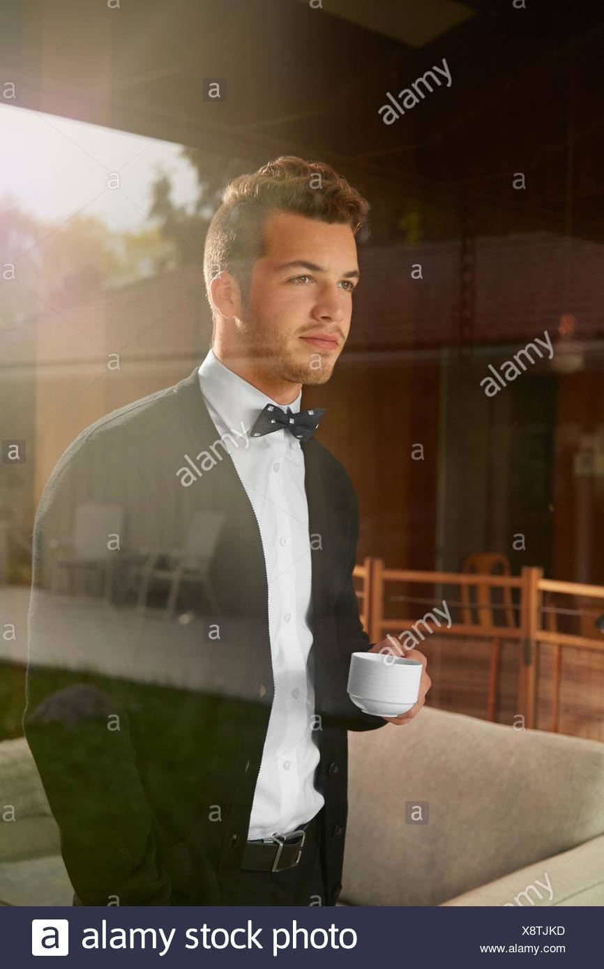 Shot through window of man standing looking out at the view holding cup of coffee - Stock Image