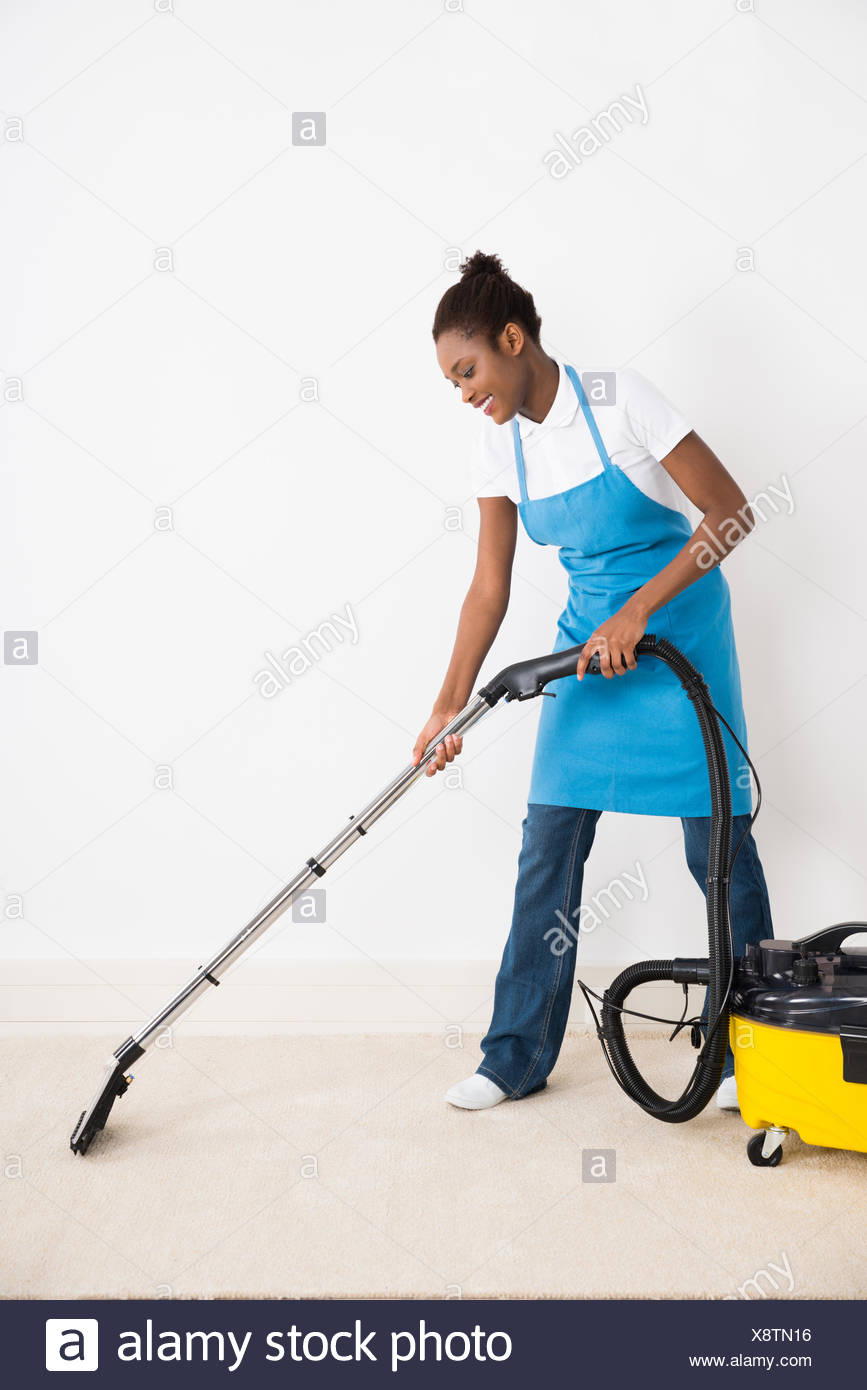 Female Janitor Using Vacuum Cleaner On Floor - Stock Image