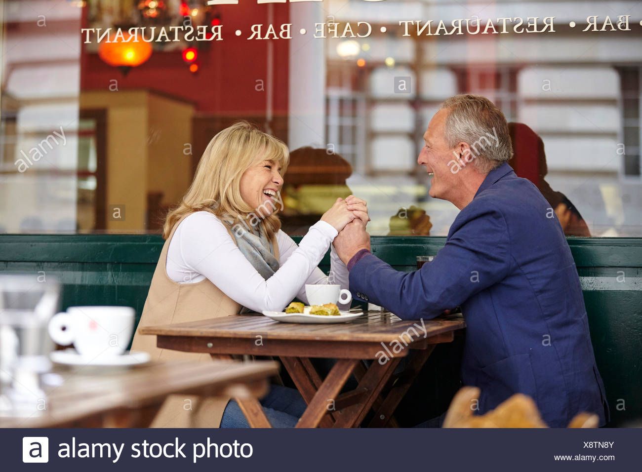 Mature dating couple holding hands at sidewalk cafe table - Stock Image
