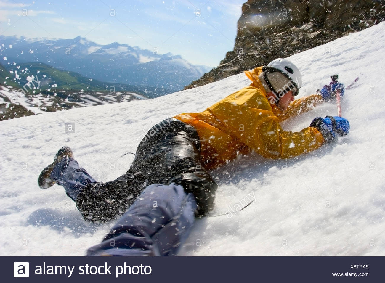 Young male mountain climber with ice axe in hands practices self arrest on Mount Ascension, Kenai Peninsula, Alaska - Stock Image