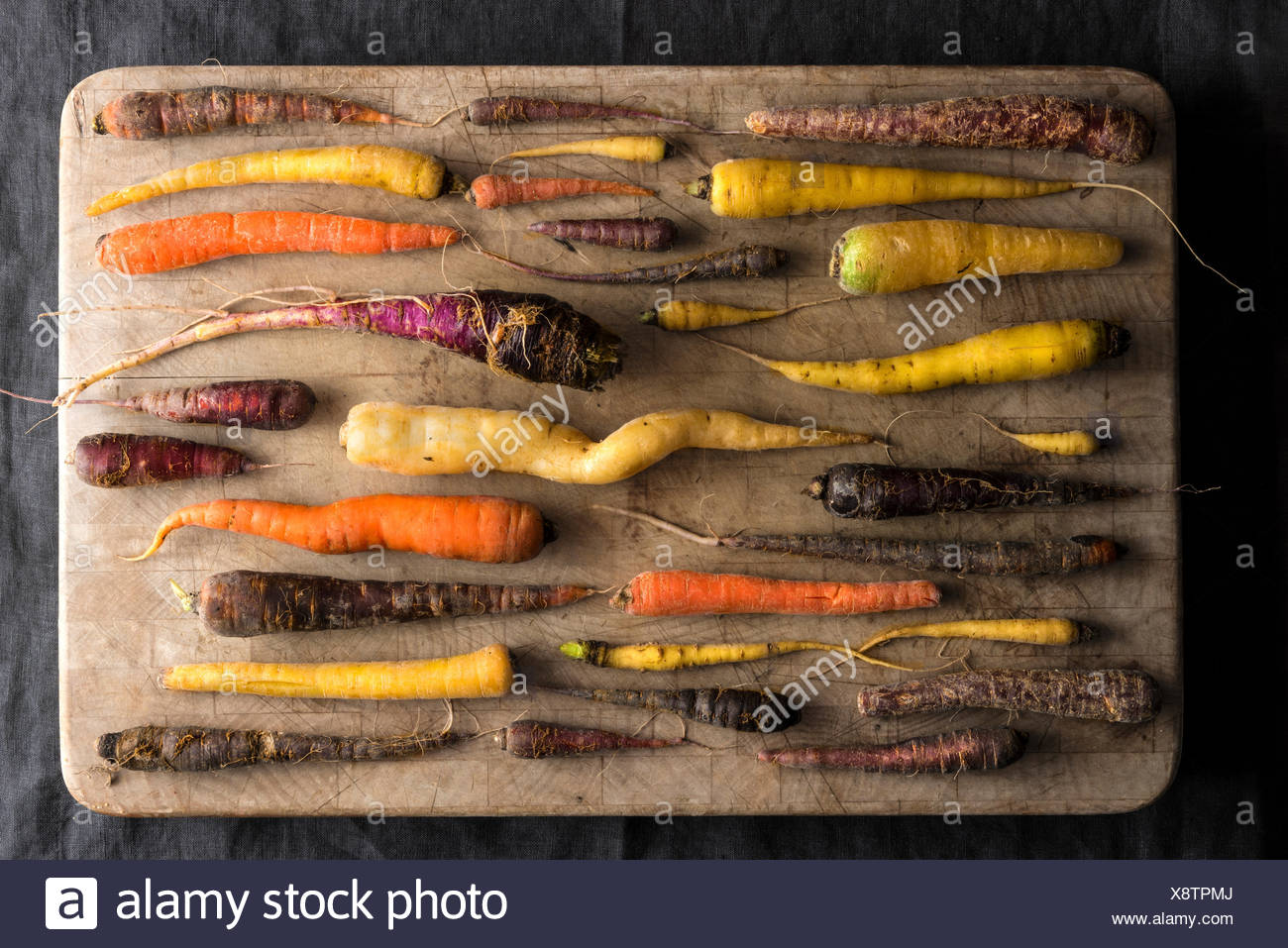 An overhead shot of an array of rainbow carrots in many colors and shapes all with a fresh from the farm, rustic look. - Stock Image