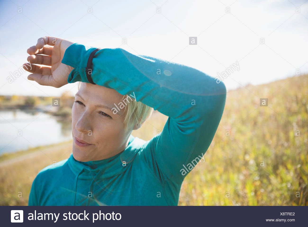 Jogger with hand on head in sunny field - Stock Image
