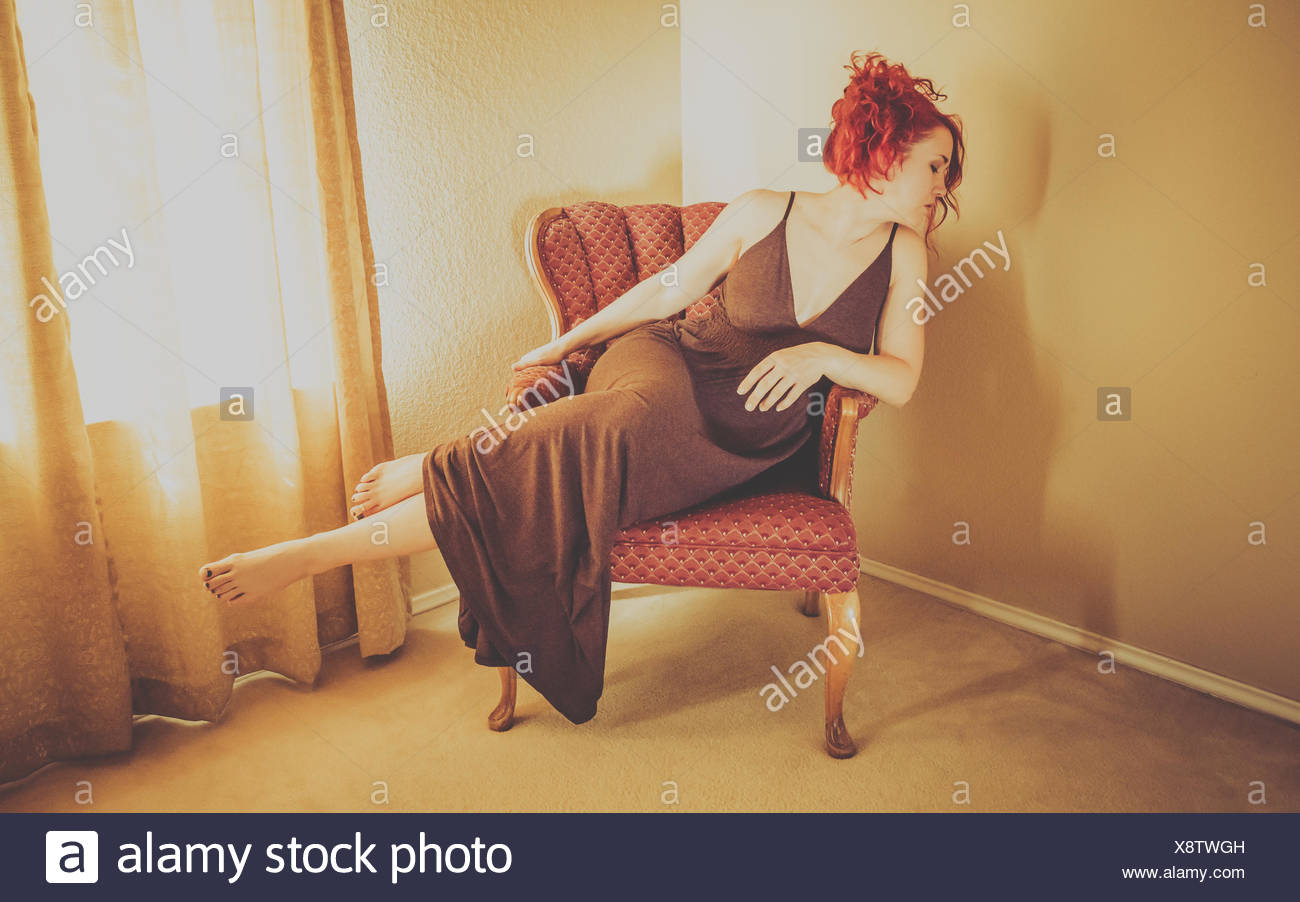 Full Length Of Fashion Model Sitting On Armchair At Home - Stock Image
