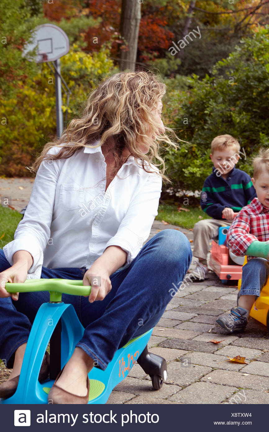 Mother and young sons riding on toy cars in garden Stock Photo