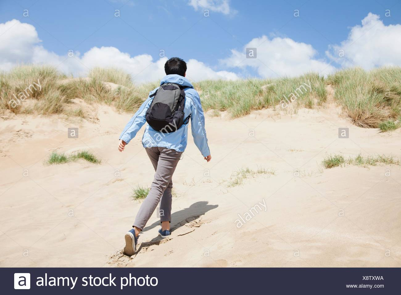 Rear view of mid adult female walker, walking up sand dune - Stock Image