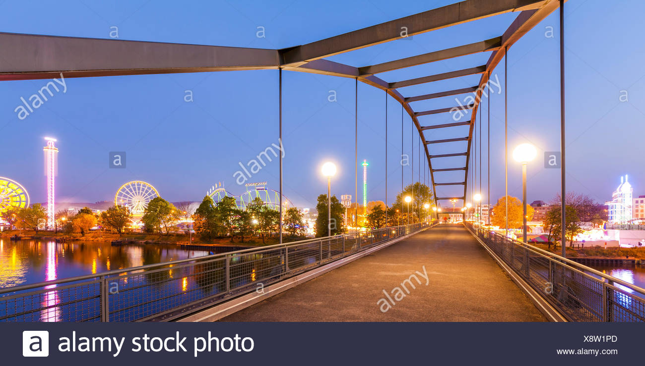 Deutschland, Baden-Württemberg, Stuttgart, Bad Cannstatt, Fluss Neckar, Fußgängerbrücke, Canstatter Wasen, Cannstatter Volksfest, Fahrgeschäfte, Achte - Stock Image