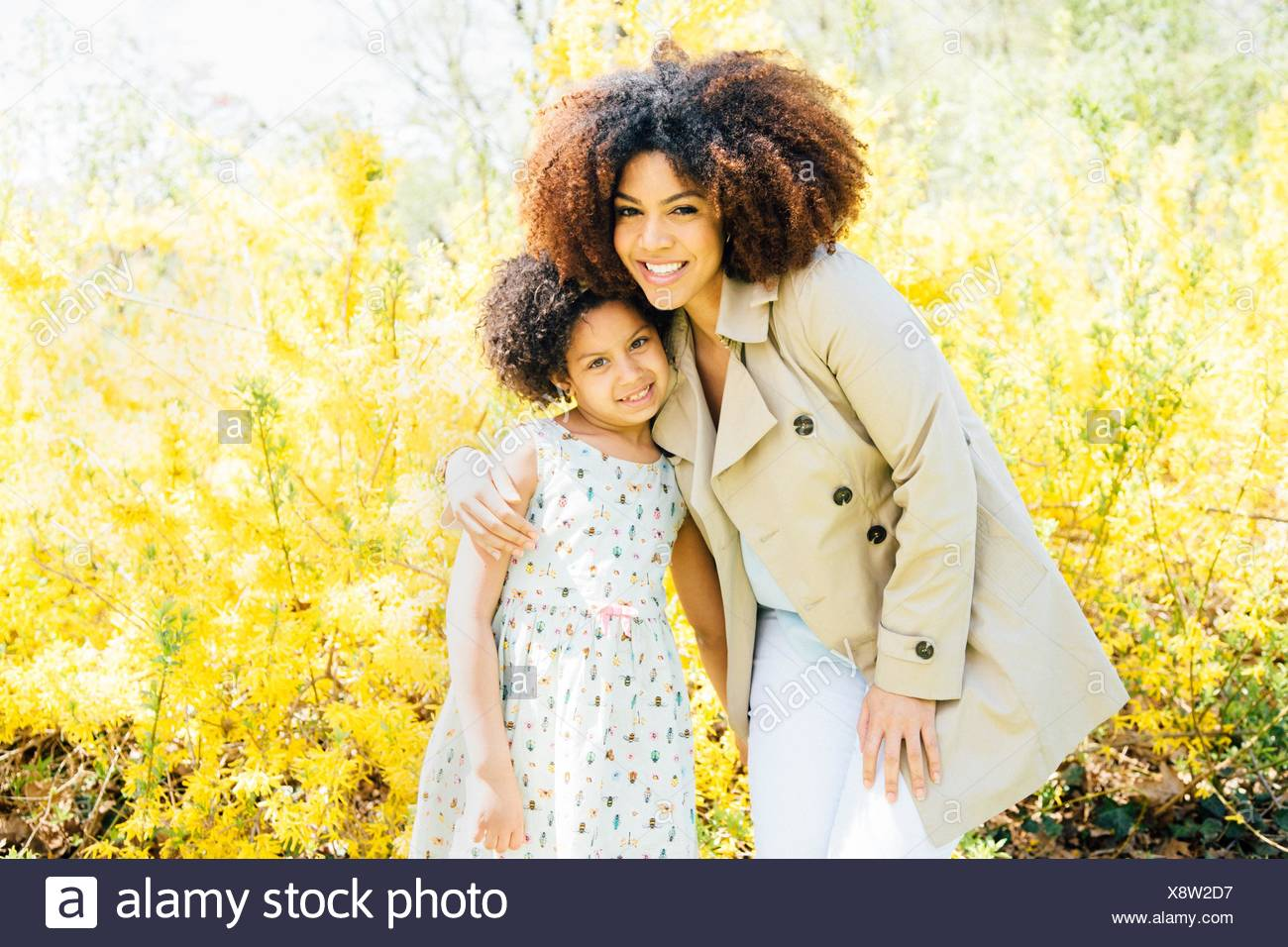 Portrait of mother with arm around daughter, looking at camera, smiling - Stock Image