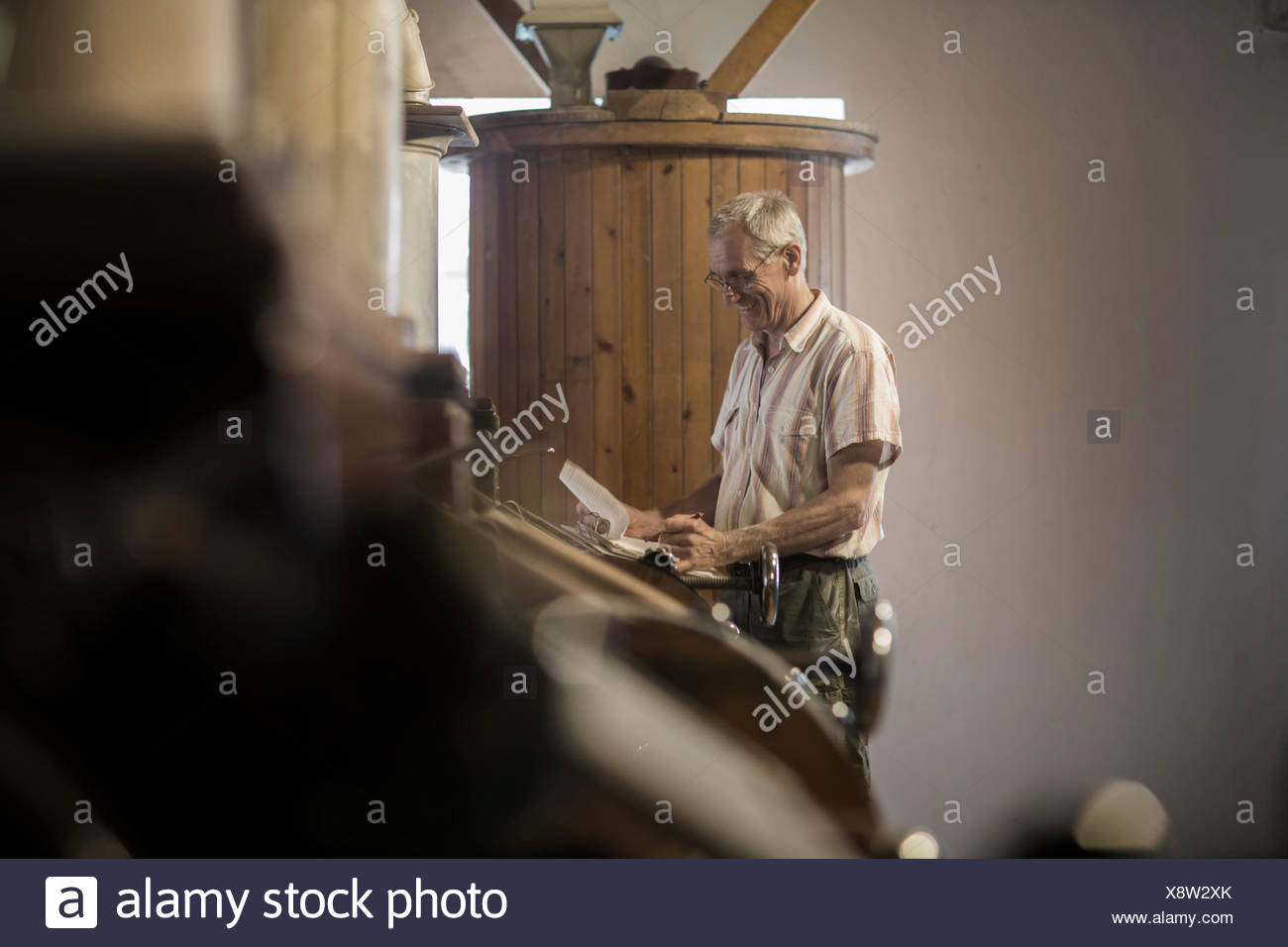 Male miller monitoring milling machine at wheat mill - Stock Image