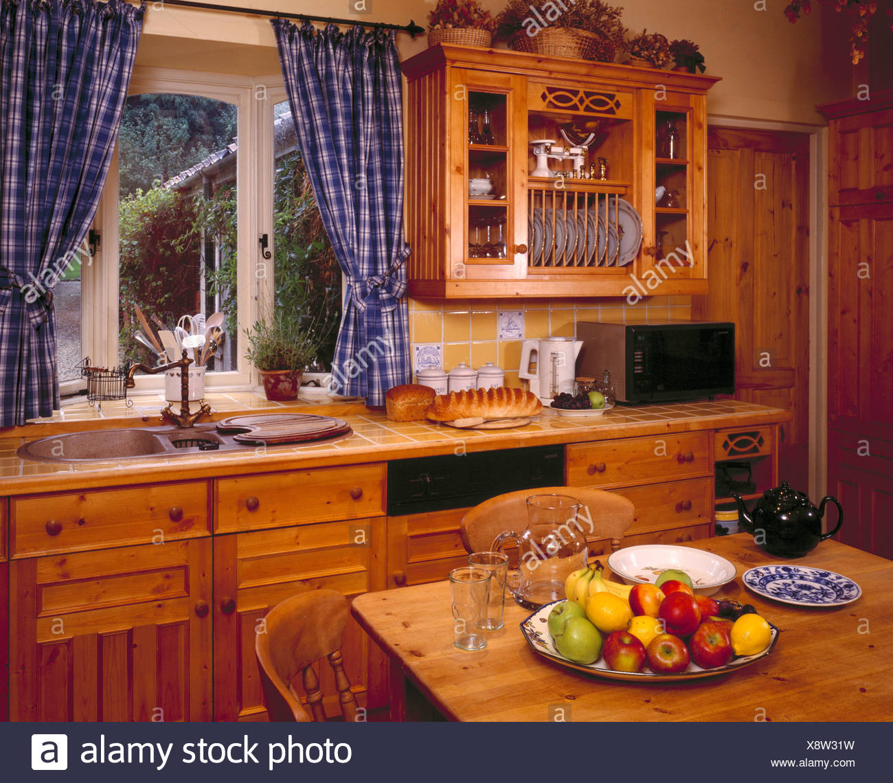 Bowl of fruit on wooden table in traditional kitchen ...