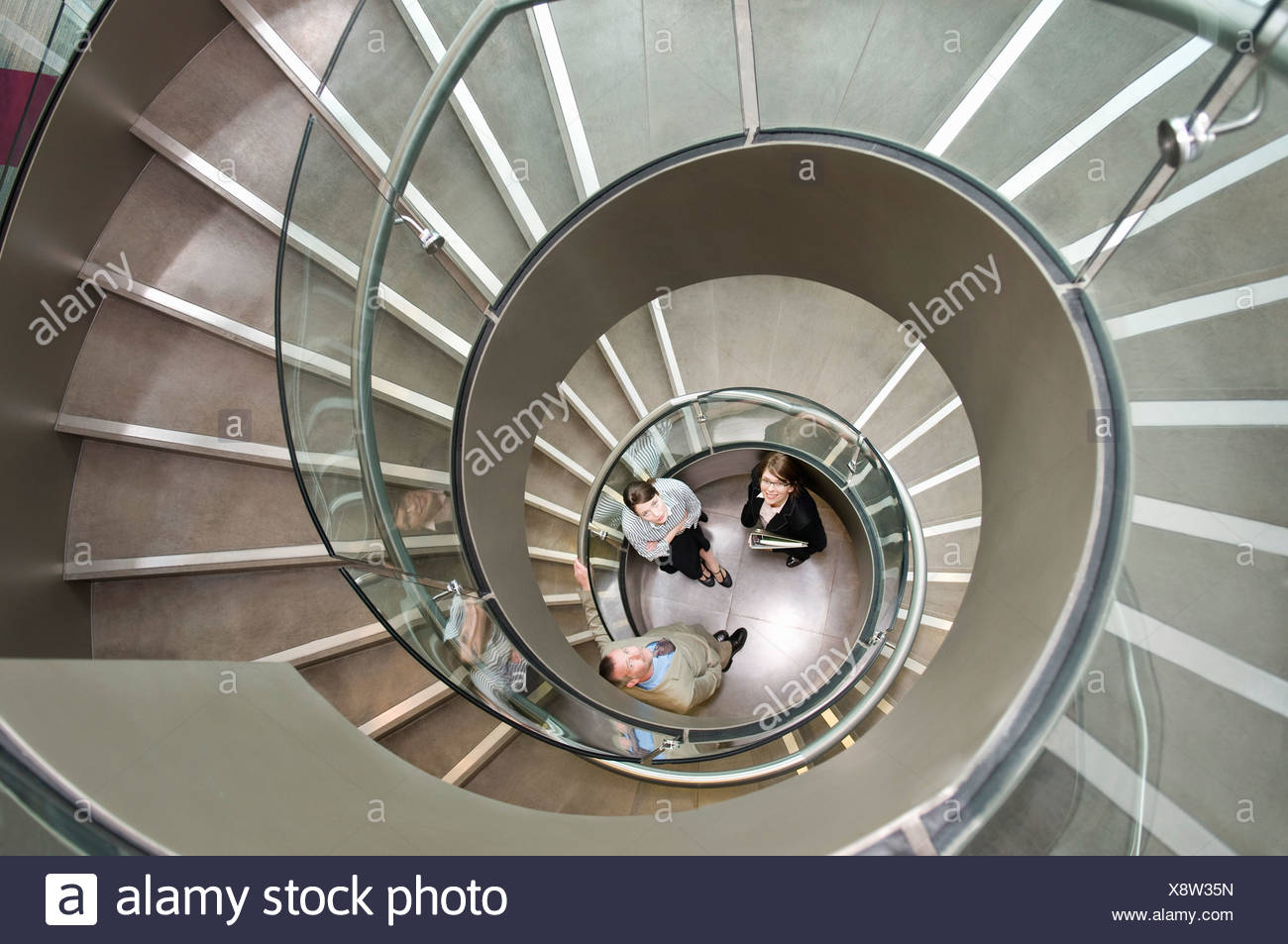 Business trio in a spiral stairwell - Stock Image