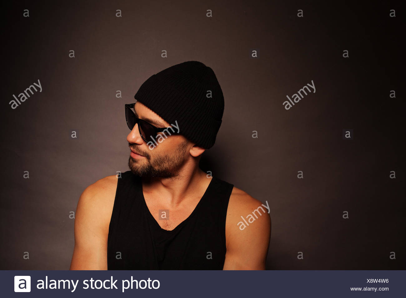 Trendy young man portrait looking away in a dark background wearing a beanie  hat 4ea017f227fe