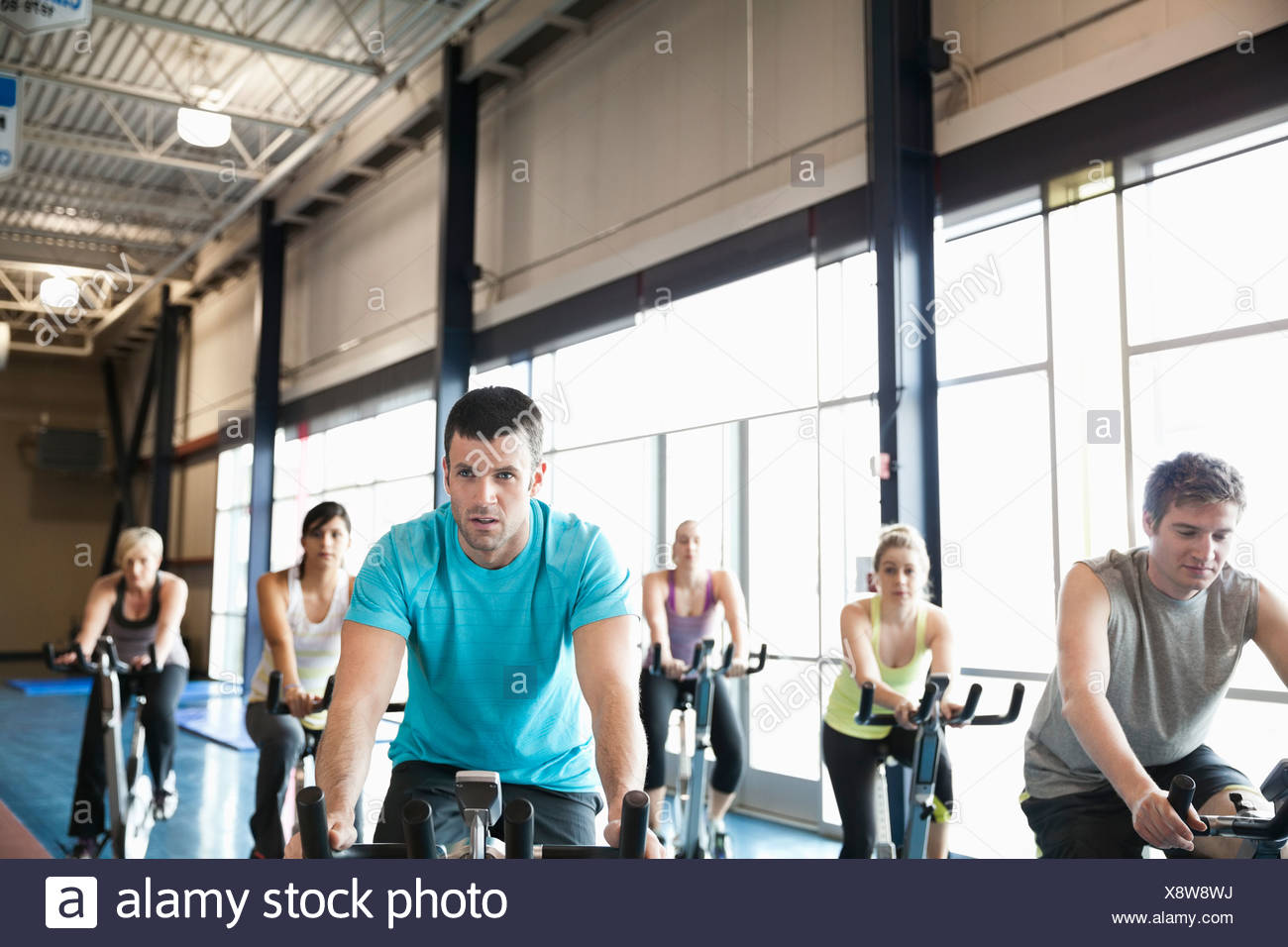 People exercising on stationary bikes in fitness class - Stock Image
