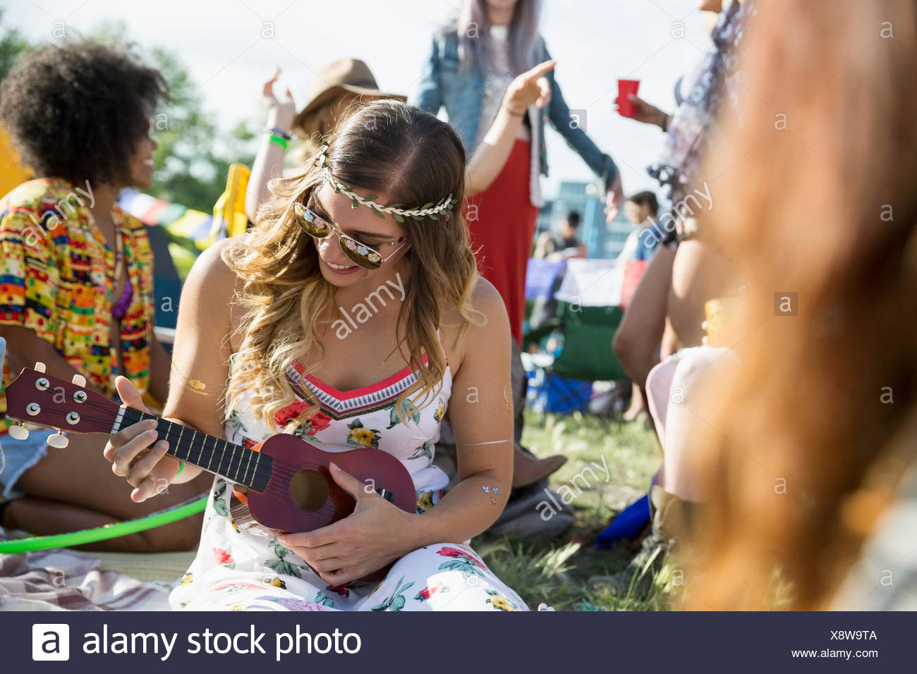 Young woman playing ukulele at summer music festival campsite - Stock Image