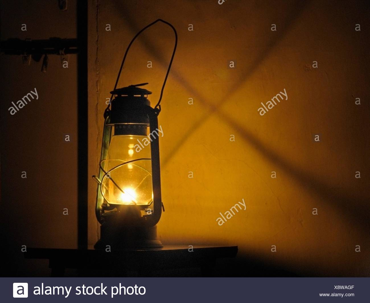 Lantern in darkness with shadow on wall  Mulshi, Pune, Maharashtra, India - Stock Image