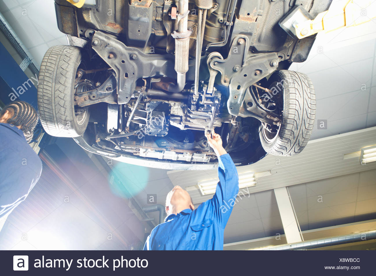 Male college student looking up at car in garage workshop - Stock Image