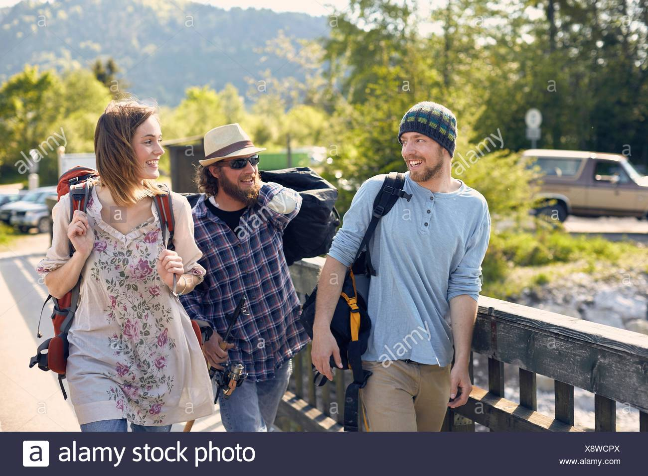 Three people walking together carrying backpacks, smiling - Stock Image
