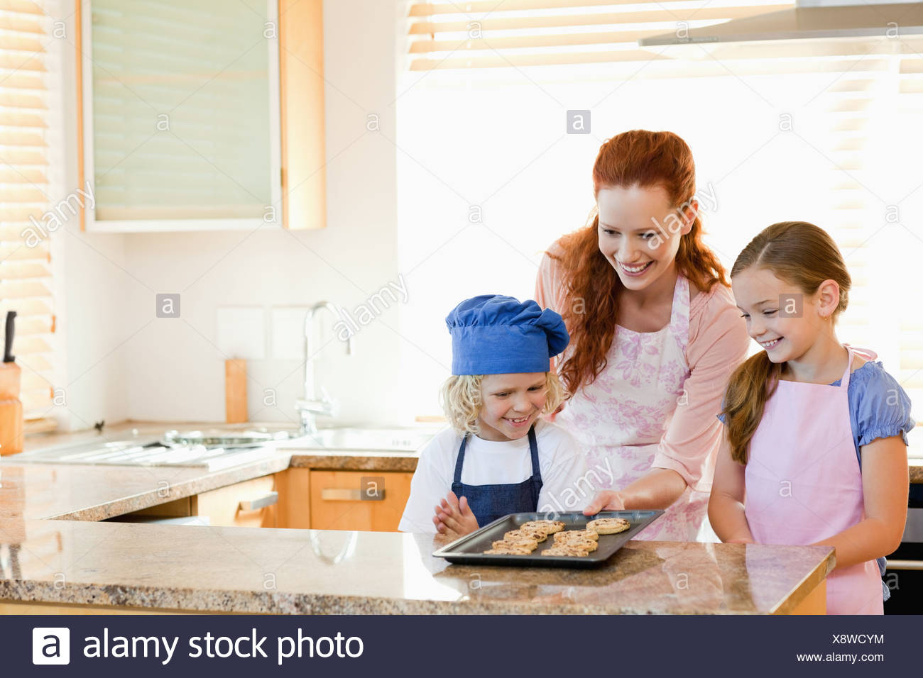 Mother presenting finished cookies to her children - Stock Image