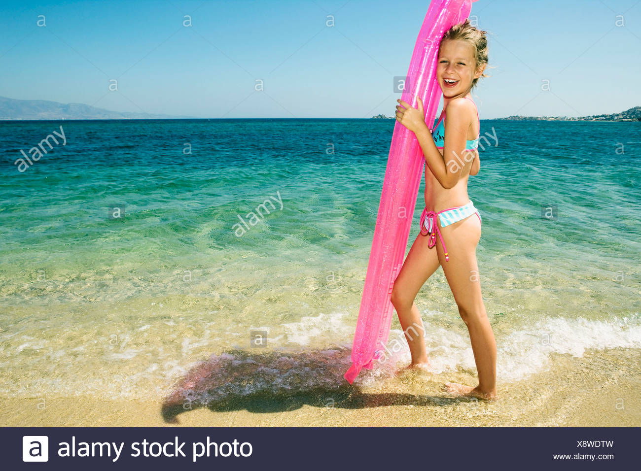 Young girl holding up an inflatable raft at the beach smiling. Stock Photo
