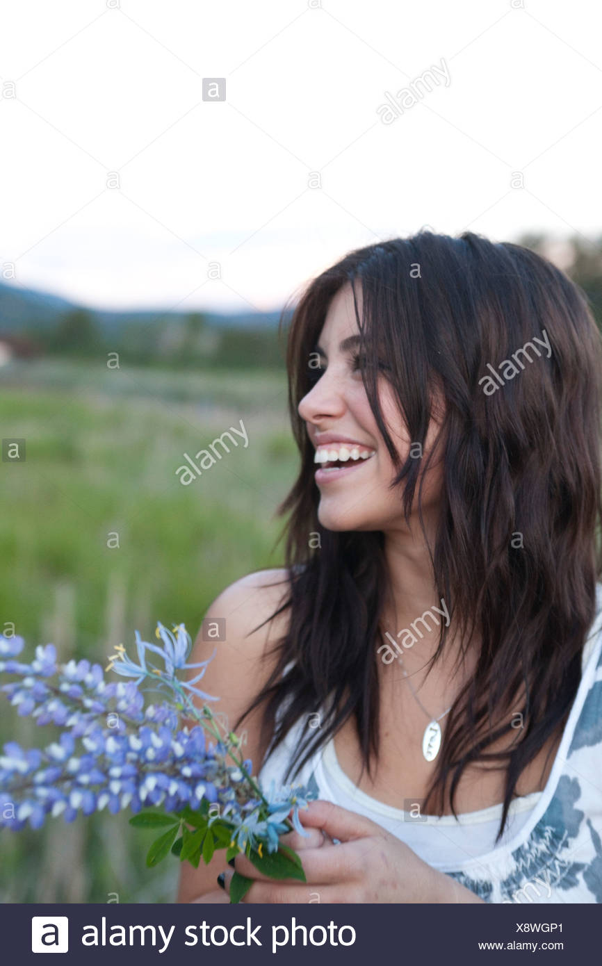 A young woman holding flowers in a green field. - Stock Image