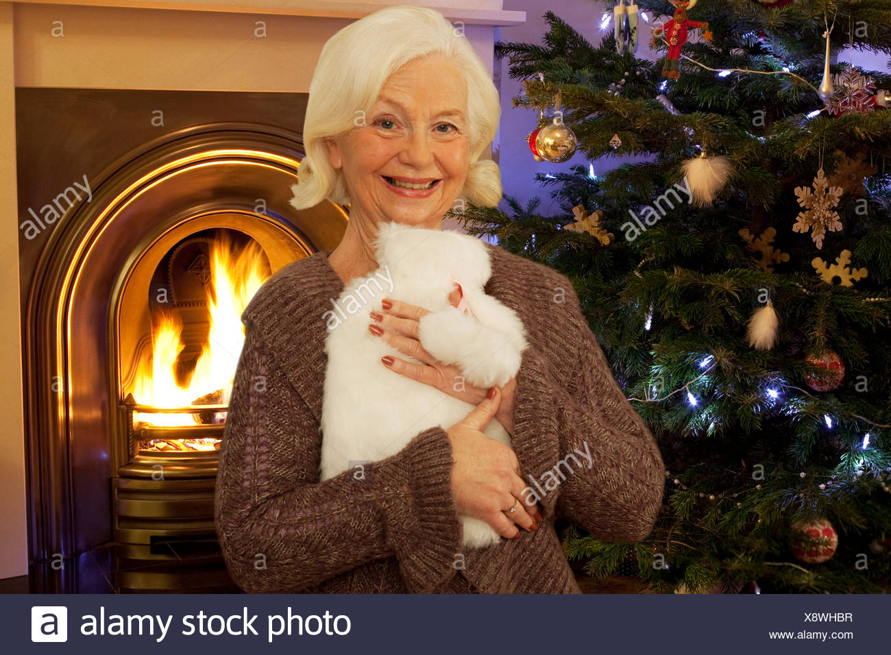 A grandmother hugging a hot water bottle - Stock Image