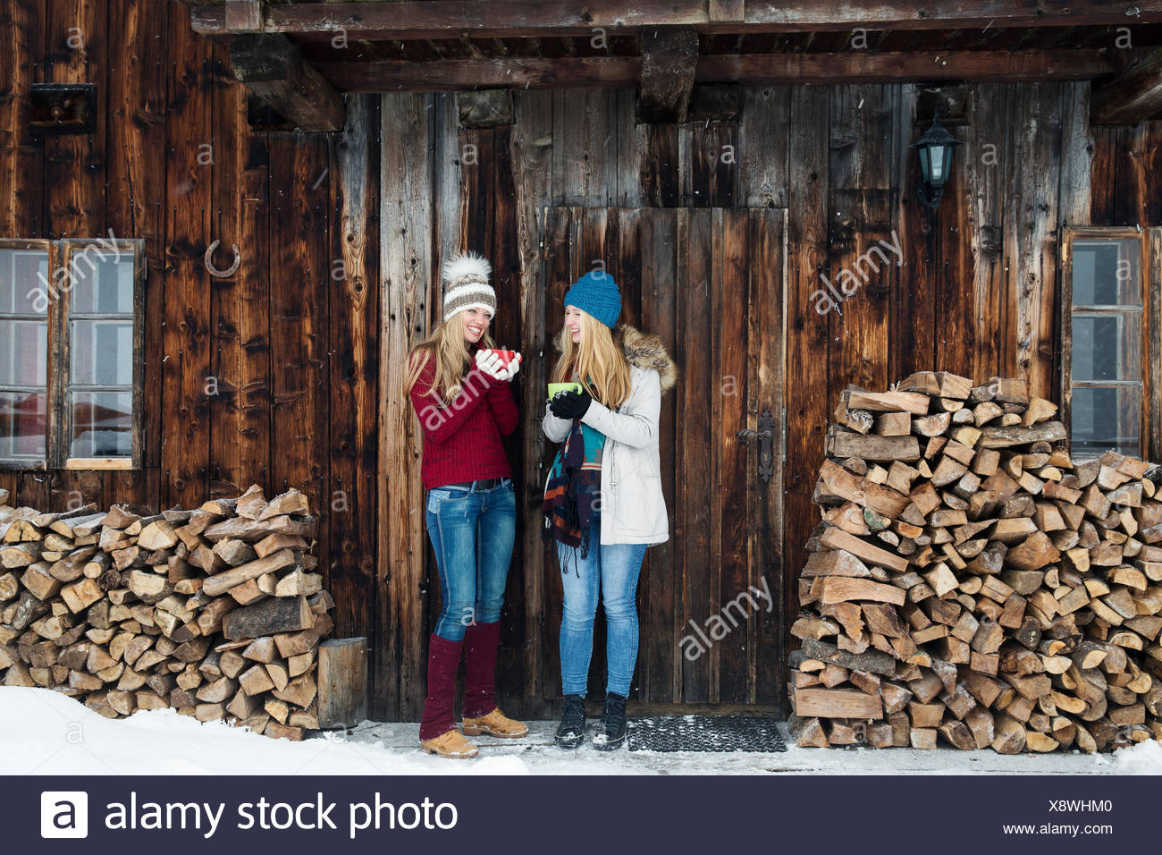Two young female friends chatting outside wooden cabin - Stock Image